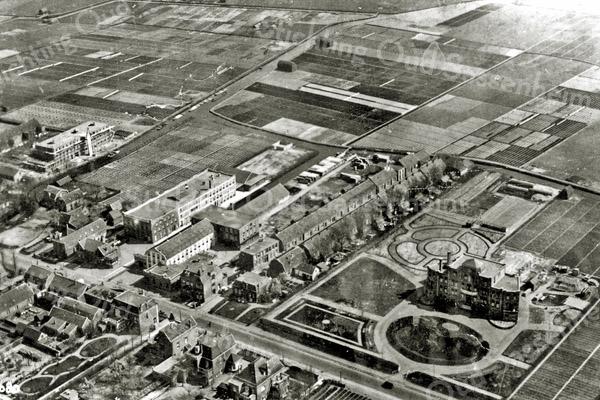 F2932<br /> Een luchtfoto van o.a. de St. Bernardus, waarvan de bouw eind 1924 voltooid was. Duidelijk is te zien hoe fraai de aangelegde tuin erbij ligt. Links vooraan de gebouwen van Baartman & Koning en van Van Zonneveld & Philippo. Tussen de twee rijen huizen ligt de Zuiderstraat. Helemaal links, aan de overzijde van de Zandsloot, de in aanbouw zijnde schuur van Bader, later van G.B. de Vroomen. De foto is gemaakt vanuit de zeppelin op 13 oktober 1929. Let op de Nederlandse driekleur op het dak bij B&K; de vlag was bedoeld als herkenning voor de heren Koning en Arentshorst die aan boord van de zeppelin waren.