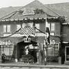 F0881 <br /> Feestelijke versiering van de Sassenheimsche Motorreederij N.V. Wesseling aan de Molenstraat tijdens het bevrijdingsfeest. Er liggen rails op de straat, mogelijk zijn die gebruikt voor het tobbetje steken. Foto: 1945.