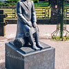 F0505<br /> Bronzen beeld van Frans van der Veld, met als titel: Zittende man op bollenmand, geplaatst in 1985. De man heeft in zijn jas een zogeheten 'damessluiting'. Op de achtergrond de pastorie van de St. Pancratiuskerk aan de Hoofdstraat. Foto: 1999.