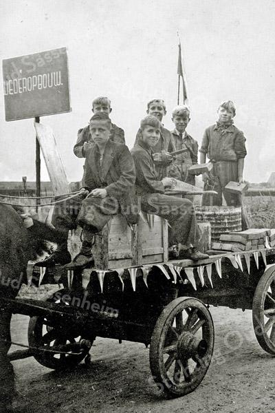 F1095 <br /> Bevrijdingsoptocht op 31-8-1945. De wagen heeft als thema: Wederopbouw. Vooraan: Piet v.d. Geest Pzn. links en Leen v.d. Kwaak. Tweede rij v.l.n.r.: Sjaak van Rijn; Bram v.d. Kwaak; Wim van Rijn en Rinus Dorrepaal. Paard en wagen waren geleend van Dirk van der Geest.
