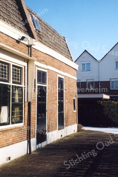F0499a <br /> Het achterste deel van het huis met kantoor van de dames Reeuwijk aan Hoofdstraat 152 (voormalig aannemersbedrijf van Th. Reeuwijk – gesloopt in 2003). In het kader van de registratie van bollenschuren, behoorde ook dit kleine exemplaar tot de collectie. Op de achtergrond de huizen aan de Hoekstraat. Foto: 1999.