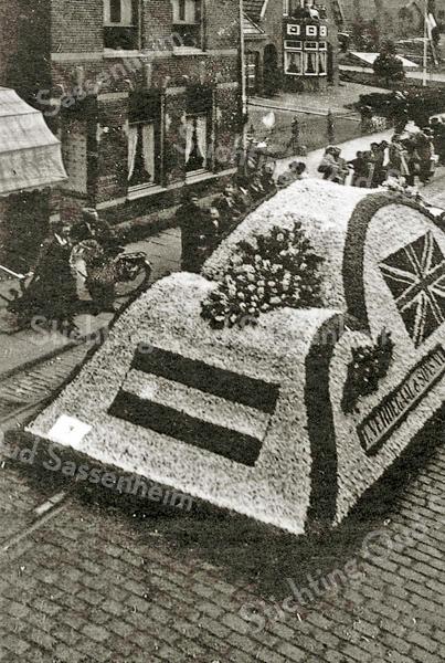F1963a<br /> De bedrijfswagen H. Verdegaal & Zn. wordt gebruikt als corsowagen in het eerste bloemencorso in 1948, vóór het huis van Koos Bakker. We zien de Nederlandse en rechts de Britse vlag. Op de andere zijkant was de Amerikaanse vlag aangebracht.