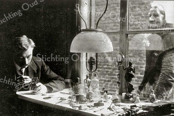F1956<br /> Horlogemaker en kunstschilder Cas Verlint in zijn jonge jaren. Het lijkt erop dat hij hier nog werkzaam is bij zijn schoonvader Saton in Rijnsburg. De aangrenzende buurt van het pand aan de Hoofdstraat/Kerklaan te Sassenheim was namelijk gescheiden door een houten schutting - en die is op de foto niet te zien. Foto: ca. 1920.