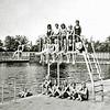 """F1534 <br /> Het oude zwembad aan de Willem Warnaarlaan.Er was de mogelijkheid tot schoolzwemmen en hier zien we klas 6 van de Visserschool op en onder de hoge duikplank aan het dameskant. Op de achtergrond zien we de kleedhokjes. Als het mooi weer was en druk, waren de hokjes snel bezet en moest je jezelf omkleden in de algemene kleedruimte ook wel het """"schapenhok"""" genoemd."""