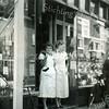 F3616<br /> Prijnie van Maanen (rechts) voor het pand van AH aan de Hoofdstraat. Foto: 22-9-1955