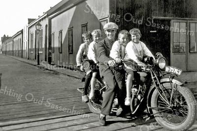 F0028 <br /> De vriend van Arie Oudshoorn, de Duitser Harold Olie met een aantal kinderen op zijn Indian motor. Achter hem de bollenschuur van Klaas Oudshoorn, achterin de Zuiderstraat. De houten brug leidt naar het bollenland van Leen van Leeuwen. Foto: ca. 1930. F0027/29/30