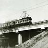 F4430<br /> Het spoorviaduct. De fotograaf heeft een mooi moment afgewacht: de tram rijdt boven een juist passerende trein, aan de zuidoostkant van de Rijksweg 4. De omgelegde trambaan werd iets eerder in gebruik genomen dan de Rijksweg zelf, officieel op 1 juni 1938.