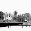 F3577<br /> De foto is genomen vanaf de Ter Leedebrug op de Van<br /> Pallandtlaan/Provinciale Weg 3. Op de achtergrond zien we villa Het Sassenest (op het eilandje Elba) met het theehuis<br /> aan de waterkant van de Leede. Rechts het hekwerk van het land van Langeveld.