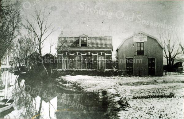 F0020 <br /> Dit woonhuis is tegenwoordig (1995) bewoond door Hans Langeveld op Hoofdstraat 104 met links de Zandsloot. Voorheen woonde hier de familie Cornelis van der Wiel, die er een handel in veevoer had en een bollenbedrijf. Rechts een houten schuur met het bord 'Depot der Leerhoeve'. De schuur is later verbouwd tot woonhuis, nu (2016) bewoond door Aad Langeveld.