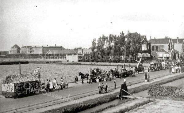 F0424 <br /> Optocht gehouden op het Oranjefeest t.g.v. het 25-jarig regeringsjubileum van koningin Wilhelmina op 13 september 1923. De foto is genomen ter hoogte van  Huize St. Bernardus in noordwestelijke richting. Links op de achtergrond het bloembollenbedrijf van C.J. Speelman & Zn. met de molenstomp. Rechts de villa's Nancy, Linquenda en Even Buiten. Rechtsonder is te zien, dat er een sloot langs de weg liep. Achter de hoge heg die naar de gebouwen van Speelman loopt, loopt het zogeheten Speelmanlaantje. Dit was een pad dat – tegenover de Zuiderstraat - vanaf de Hoofdstraat tussen villa Even Buiten (Hoofdstraat 89) en villa Transforma (afgebroken in 1965) liep en de toegang vormde naar het erachter gelegen bollenbedrijfscomplex van Speelman. Foto: ca. 1923.