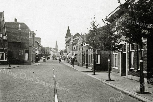 F0975 <br /> Hoofdstraat, gezien vanuit noordelijke richting. Midden in het beeld zien we het torentje van de sigarenwinkel van Barend van Loo. Rechts is de ingang van de Burchtstraat te zien, met op de hoek kapper Uphoff. Foto: ca. 1951.