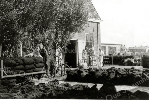 F1164a <br /> De narcissenkokerij van Ab Helmus aan de Zandslootkade. Hij staat achter de kar met naast hem zijn zoon Rien. Links van de trap staat zijn zoon Bert. Zijn dochtertje Cate staat achter de poppenwagen. In 1948 is Ab Helmus met de narcissenkokerij begonnen. Nadat het pand in 1959 was verbouwd tot het kantoor van A. Frijlink & Zn., is het in 1979 gesloopt. Nu is hier de Prins Clausstraat. Foto: 1950.