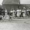 """F2857 <br />  De Oranjefeesten van 1923, op de voorste fiets van deze groep deelnemers met versierde fietsen staat de spreuk """"Hulde aan de Koningin"""". Op de achtergrond zien we het kantoortje van de haven met daarachter de schuur van van Deursen en links nog de huizen die aan de Nieuwe Haven (Concordiastraat) stonden."""