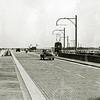 F4441<br /> Prachtig zicht op de Rijksweg vanaf het viaduct over de spoorlijn. Links in de verte zien we de watertoren van Sassenheim. Rechts de tram bij het begin van de afrit. Merk op dat de weg met klinkers bestraat was. Vangrails bestonden nog niet. De middenberm werd tijdens de oorlogsjaren door sommige ambtenaren van Rijkswaterstaat gebruikt om moestuintjes aan te leggen. <br /> Vanaf 1961 heette deze weg Rijksweg 4a (Rijksweg 4 ging vanaf toen bij Burgerveen rechtdoor) en vanaf 1968 is het de A44.