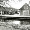 F1351 <br /> De Vaartkade met de asschuur (gesloopt in januari 2002). Tot voor circa 6 jaar was hierin schoenmaker H. Warmerdam gevestigd. Op de deur is het opschrift 'Schoenmakerij de Molen' nog te lezen. Rechts is nog net het huis van de fam. Van der Willik te zien, dat later de moskee werd. Links het voormalige huis van aannemer C.J. Melman. Foto: ca. 1910.