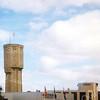 F0388 <br /> De voormalige watertoren aan de Wasbeekerlaan. Het water werd vroeger naar boven gepompt om druk op de waterleiding te krijgen. Die functie is nu weggevallen en het pand werd door bouwbedrijf Meijer gekocht, dat hier de vlag in top heeft. Meijer is van plan boven in de toren een restaurant te vestigen, maar dat is uiteindelijk niet doorgegaan. Op de voorgrond een van de nieuwe bedrijven (Hedera) op het bedrijventerrein Wasbeek, gezien vanaf rijksweg A44. Foto: 1997.