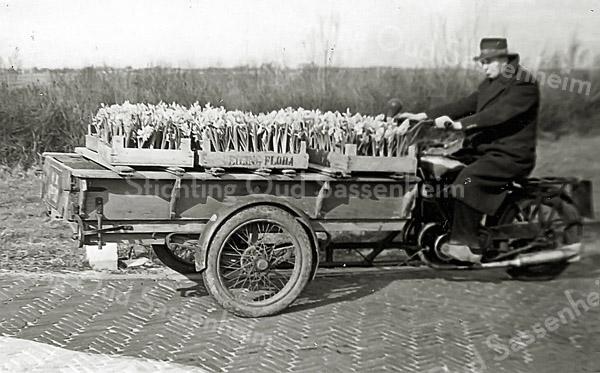 F0230 <br /> Arie van der Veer met een motorbakfiets (opname van 2-3-1951). Hij gaat naar de veiling Flora in Rijnsburg. Arie was een kleine kweker en moest vroeg in de ochtend zijn bloemen naar de veiling brengen.  Foto: 1951.