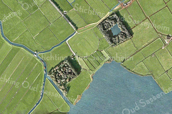 F0939<br /> Luchtfoto van een bijzonder gebiedje (op Warmonds grondgebied) aan het eind van de Menneweg. Linksonder zien we de voormalige vuilstortplaats en rechtsboven de eendenkooi. <br /> De gemeente heeft de voormalige vuilstortplaats een recreatieve bestemming gegeven. Bijna alle bomen zijn gekapt en een groot deel van de grond is afgegraven. Vervolgens is de grond een meter opgehoogd, met daaronder een beschermlaag. Het grondoppervlak is golvend geworden en er zijn nieuwe bomen geplant. Achteraan is een uitkijkpunt met zich op de Kagerplassen.