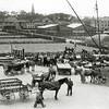 F0668 <br /> Bedrijvigheid aan de Oosthaven in vroeger jaren met nog veel vervoer met paard-en-wagen. In het water verscheidene binnenvaartschepen. Het schip, dat geladen/gelost wordt is de Sassenheim IV van  de Sassenheimsche Motorrederij N.V. Dit schip heeft Joh. Bakker in 1927/1928 nieuw laten bouwen en kreeg de naam van zijn echtgenote, Adriana. In 1936 kocht opa een groter schip en verkocht hij vervolgens de Adriana aan Wesseling. Wesseling gaf het de naam Sassenheim IV.  Het schip is trouwens -onherkenbaar verbouwd - nog steeds in de vaart en doet dienst als rondvaartboot in het bekende Safaripark 'de Beekse Bergen' bij Hilvarenbeek onder de naam Livingstone.<br /> <br /> Op de achtergrond bollenvelden met een rietschelft. Links boven is het eerste huizenblok verrezen langs de Bijweglaan-in-wording. Rechts de houttuin van de fa. M. Bakker & Zn., de bollenschuren van L. v.d. Voet, Aangeenbrug, Vlasveld en B.D. Kapteyn & Zn. C.V. Verder de huizen langs de Kerklaan en de chr.-geref. Kerk (links op de foto).  Deze foto is waarschijnlijk tijdens de Tweede Wereldoorlog genomen.  Vrachtwagens waren toen in beslag genomen door de Duitsers; daarom was er veel vervoer met paard-en-wagen.