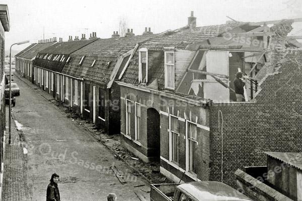 F3843<br /> De Zuiderstraat in vroeger jaren. Men is begonnen met de sloop van de panden om plaats te maken voor nieuwbouw. Behalve de 2 grotere huizen rechts vooraan bestaat de straat uit typische arbeiderswoningen van begin deze eeuw. Let op de klinkerstraat voor de ramen. De Zuiderstraat is gesloopt in 1975-1977.