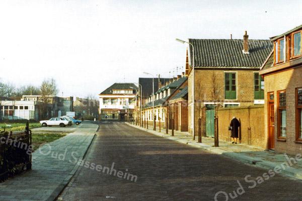 F0297 <br /> De Kerklaan (noordkant) gezien richting Hoofdstraat. De huizen aan de linkerzijde zijn in 1975 gesloopt. Links de achterkant van de winkel van Albert Heijn en we kijken recht op hotel-café-restaurant 't Bruine Paard met verder weg de huizen aan de Hortuslaan. Uiterst links het hek van de voortuin van Dick van Leeuwen, Kerklaan 44. Voorbij de groene poort zien we de voormalige bollenschuur van Jan Pereboom, op deze foto Kunstaardewerkfabriek Velsen, met daar vlak achter de bijbehorende showroom. Foto: 1976.