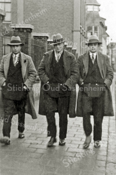 F2701<br /> De heren Cees Batenburg, Jan Faas en Piet de Kwaasteniet wandelend bij het Verenigingsgebouw, nu parkeerplaats voor de Ned. Hervormde Kerk. Foto: 1933.