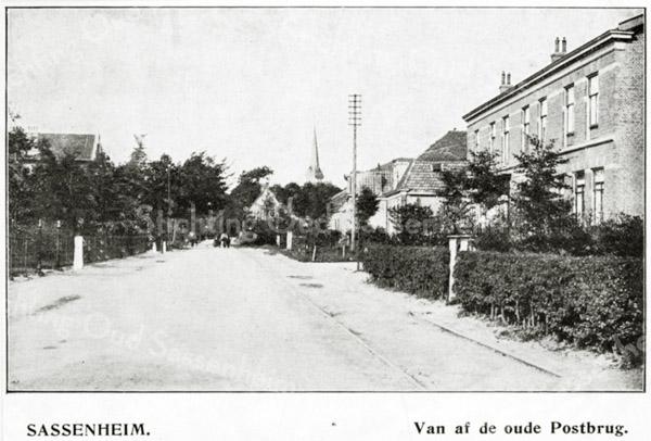F0413 <br /> Stukje Hoofdstraat, gezien vanaf de Oude Postbrug. In het eerste pand rechts woonde Aagje Nipper, naaister. Verder de winkelpui van bakker G. Lekkerkerker, die het bedrijf in 1920 verkocht aan L. van Vliet. Het pand daarnaast staat op de hoek van de Hoekstraat. Op de achtergrond zijn het tolhuis en de oude toren van de St. Pancratiuskerk te zien. Rechts in de weg liggen de tramrails van de stoomtram. Foto van begin 20ste eeuw.