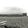 F1423 <br /> De DKW-autofabriek aan de Warmonderdam, gezien vanuit het oosten. Links rijksweg 4 (vanaf 1976 A44). Rechts de huizen langs de Warmonderdam. Op het dak de naam Hart Nibbrig & Greeve N.V. Later was hier Mitsubishi gevestigd en Auto Union. Foto: ca. 1950.