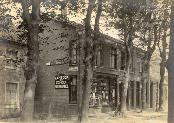 F0780 <br /> Voort aan de Hoofdstraat te zien, dat in 1980 werd afgebroken voor de op die plek te bouwen winkel van Jolentha Mode met bovengelegen appartementen. Daarnaast zien we winkelhuizen die gebouwd werden in 1895 voor rekening van dokter Metzlar. Het lage pandje daarnaast bestaat niet meer. Vele jaren was in de eerste winkel Van Steijn gevestigd. Later was hier een videotheek en nu al vele jaren een modezaak. Foto: vóór 1921.<br /> <br /> [Collectie Oudshoorn 008: winkelhuizen dr. Metzlar 1895. Ammerlaan.]