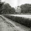 F1251 <br /> Op deze foto van rond 1900 zien we de oprijlaan naar Het Oude Koningshuys. Links van de oprijlaan ligt Casa Reale. Het voormalige gemeentehuis aan de Wilhelminalaan is vooraan op deze oprijlaan gebouwd. De Wilhelminalaan is rechts van de heg aangelegd.