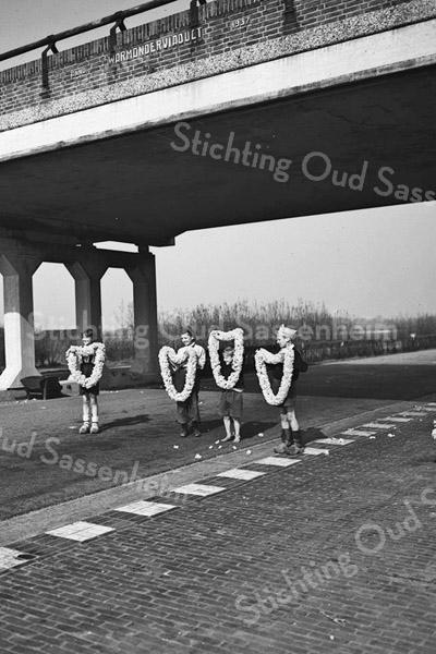 F3645<br /> Kinderen met bloemenslingers onder het Warmonderviaduct. Foto: 1946