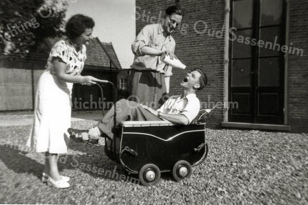 F0590<br /> Kantoorpersoneel van Baartman & Koning N.V.  V.l.n.r.: Hennie v.d. Voort, Klaas Smit in de kinderwagen en Cornelis van Diggele die de fles geeft. Foto: 1951.