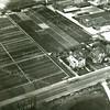 F3073<br /> Luchtfoto van de villa's Nancy (links) en Linquenda (rechts). Bovenaan de foto zien we in het midden het bollenbedrijf van Speelman met de molen. In de rechter bovenhoek zien we de Zandsloot. Onderaan is de vijver van de Bernardus. Let op de prachtige bollenvelden tot aan de Hoofdstraat. Foto: vóór 1960.