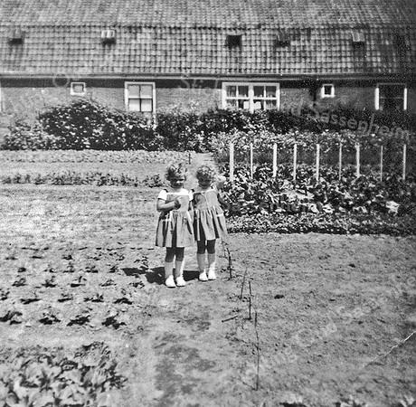 F0010 <br /> De tweelingzusjes Hogewoning. Ida (links) en Gerda (rechts), dochters van Albert Hogewoning in de groentetuin van Stelma met 4 van de 6 huizen aan de Boschlaan. Het huis in het midden heeft op deze foto een dubbel raam. In 1976 is de buurt gesloopt. Foto: ca. 1964.