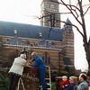 F1817a <br /> De plaatsing van twee nieuwe lantaarns op de gerestaureerde pilaren bij de St. Pancratiuskerk. Pastoor Owel kijkt toe. De man in blauwe overall is Wim Stut.<br /> Foto 2001.