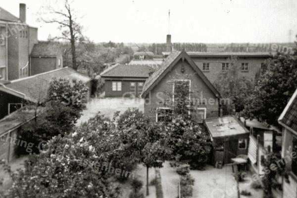 F0569 <br /> Gezicht vanuit het huis van de fam. Van der Voort (Hoofdstraat 169) op de oude bollenschuur. Daarachter staat dwars de 'nieuwe' schuur, gebouwd in 1927 en het kantoor. De oude schuur op de voorgrond heeft dhr. Van der Voort sr. in 1922 gekocht en zijn zoon Leo heeft beide schuren in 1960 verkocht. Na de sloop hiervan werd daar het Koningspark gebouwd. Links is nog de St. Annaschool te zien. ( nu de Vomar). Foto: 1954.