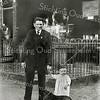 F0339 <br /> Opa Hein Perfors met kleinzoon Henk voor de schilderswinkel aan de Hoofdstraat, vlakbij de Oude Post. Links op de achtergrond het woonhuis, in de deuropening opoe Perfors. De winkel had een donkergekleurde pui en was door een ijzeren hekwerk van de straat gescheiden, wat in die tijd gebruikelijk was. Foto: 1918.