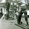 F2469<br /> Het plaatsen van een grote kerstboom op de Hoofdstraat op het plein voor de Dorpskerk. Rechts het in 1985 geplaatste bronzen beeld De mandenophaler, vervaardigd door de Lissenaar Frans van der Veld. Foto: 2001.