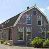 F0739 <br /> Boerderij van P.W. Langeveld Jaczn., Parklaan 22, bereikbaar via een toegangspad dat loopt vanaf de Parklaan. De boerderij stamt uit 1875 en had oorspronkelijk een toegangsweggetje dat uitkwam op de Hoofdstraat (het Homanslaantje). Bij de aanleg van de Parklaan in 1951/52 verviel het laantje. Rechts achter de boerderij zien we de daken van de Floris Schoutenstraat. Foto: 2003.