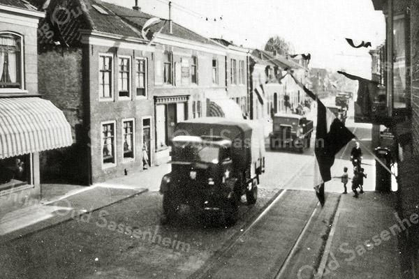 F0179 <br /> De intocht van de Canadese troepen in mei 1945. Hier is een konvooi van vrachtwagens te zien. De foto is genomen aan de noordzijde van de Klapbrug (Hoofdstraat). Links de groentewinkel van Nederstigt. Foto: 1945.