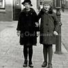 F0206 <br /> Twee meisjes op de Hoofdstraat, ter hoogte van waar nu het dorpsplein is voor de Dorpskerk. Het meisje links is Reina Geerling, het meisje rechts is Rie Faas. Op de achtergrond rechts het huis van G. Vlasveld en links daarvan het pand van Bruijnen. Daarnaast bij de elektrische klok de winkel van Jamin. Links de kapperszaak van Jan de Jong. Foto:  ca. 1932.