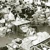 F1823 <br /> Op deze foto uit eind jaren '60 zien we een deel van het naaiatelier van de Hygia aan de Menneweg. De modinettes stellen hier baby- en kleuterkleding samen. De lapjes stof werden vooraf gesneden in de snijafdeling. Vooraan op de foto wordt alles nog eens nauwkeurig gecontroleerd, voor het naar het magazijn gaat. In een andere afdeling van het gebouw werden plastic babybroekjes geproduceerd, door middel van het zogeheten 'frequent lassen' – destijds uniek in Nederland. Foto: 1962.
