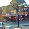 F0287 <br /> De Hoofdstraat in het centrum, nu aan de oostkant, gezien in zuidelijke richting. Links het pand van modezaak Melman, daarnaast de schoenenwinkel van Witte. Verder het technisch bureau en winkel van Kees Luijk en de juweliers- en brillenzaak van Trossèl, later Groeneveld. Het pand van Luijk is gekocht door poelier Roelofs. Nu (2016) is daar al vele jaren bakker Van Maanen gevestigd. De schoenenwinkel van Witte is vervangen door schoenenwinkel van Van der Riet. Links van het pand van Witte was een doorgang naar achteren, waar aannemer M.J. van Breda zijn werkplaats had.