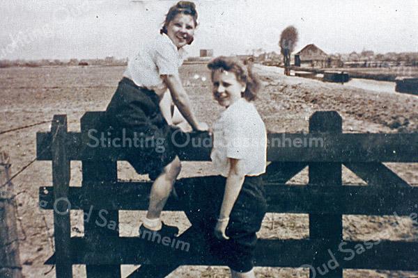 F0013 <br /> We zien links Lenie Meeuwissen (geb. 1922) met een vriendin op het hek bij de Scheisloot bij de Stenen Brug, vlakbij de Zandslootkade. Tussen de hoofden is de Ruïne van Teylingen te zien. Rechts de schuur van Vos, de kolenboer.