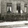 F2233<br /> Op Rusthofflaan 4 zien we links Aad van Rijn, dan zijn broer Piet en rechts naast de deur hun stiefbroer Henk van Rijn. De naam van de kleuter is niet bekend. Foto:1949.