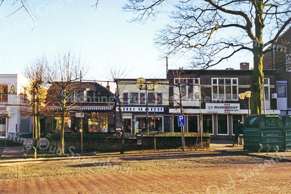 F0493b <br /> Het winkelcentrum van Sassenheim aan de Hoofdstraat met een afgebakend voetgangersgebied en de omleiding voor het autoverkeer langs de Ned.-herv. kerk of Dorpskerk. Thans is de bestrating geel en grijs gekleurd, gescheiden door een rij banken. De groentewinkel van Faas, slagerswinkel van Van den Berg en bakkerswinkel van Wanninkhof zijn inmiddels verdwenen. Nu staan hier moderne winkels met appartementen. Foto: 1999.
