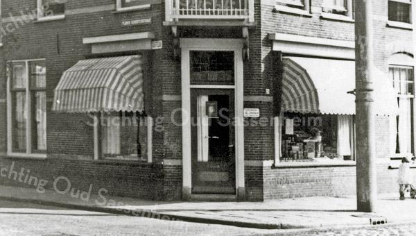 F0934 <br /> De kruidenierswinkel van Karel Eikelenboom op de hoek van de Floris Schoutenstraat. Ten tijde van de opname was de zaak blijkbaar nog niet aangesloten bij de Spar. De winkel was zelfstandig in de periode van 1939-1963. Let op het bordje 'Turkenburg Zaden' naast de winkeldeur. Nu (2016) is hier schoonheidssalon C'est ca.  Ook was hier vele jaren een groente- en fruitzaak. Foto: tussen 1939-1963.
