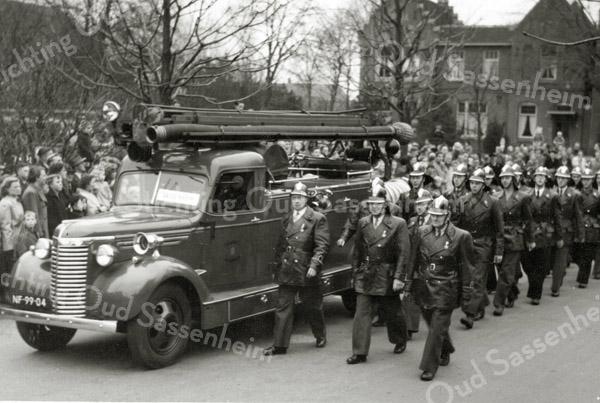 F1048 <br /> Wilhelminalaan. Het defilé op 11 november 1953 van het korps Vrijwillige Brandweer Sassenheim tijdens het 100-jarig bestaan van het korps. De eerste drie personen v.l.n.r.: M.J. van Breda; J.v.d. Meer en E. Dijkstra. Op de achtergrond de pastorie van de St. Pancratiuskerk.