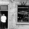 F0711 <br /> Vleeschhouwerij en Spekslagerij van Th. J. van de Meij, Hoofdstraat 167 (oude nummering). Het pandje stond op de plaats waar nu het dorpsplein is. De foto is vermoedelijk genomen op Koninginnedag, gezien de W boven het raam en de gevelversiering. De baas staat in de ingang met vóór hem een drietal smeltende ijsblokken. Foto: ca. 1910.