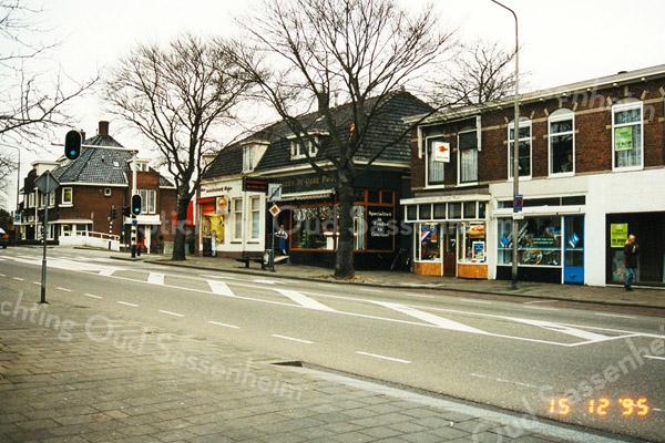 F1998<br /> Het donkere pand in het midden is slagerij De Oude Post, Hoofdstraat 117. Vanouds bekend als de winkel van de gebroeders Couvée. Het pand links van de slagerij is een bakkerij en rechts is de sigaren- en kapperszaak van Jan Karremans. Foto: 1995.